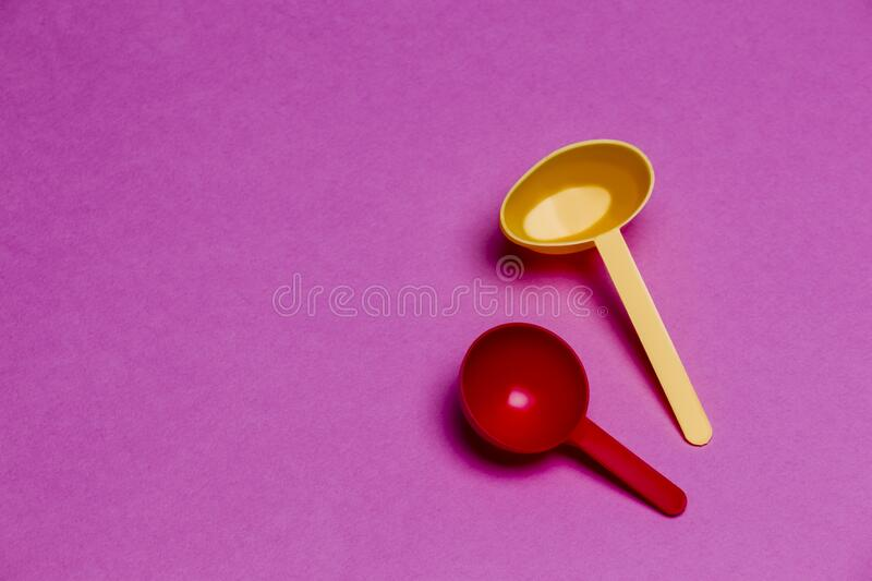 Pair of Colorful Plastic Spoons Placed Together Over Colorful Pink Background royalty free stock image