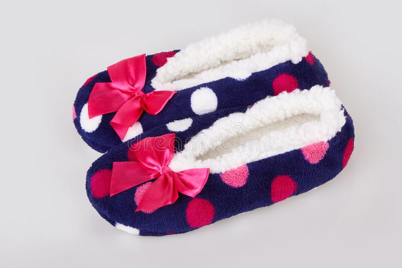 A pair of colorful polka dot patterned warm cozy slippers with pink satin bows royalty free stock photography
