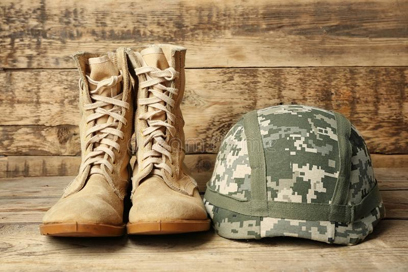 Pair of combat boots and military helmet on wooden background, royalty free stock photo