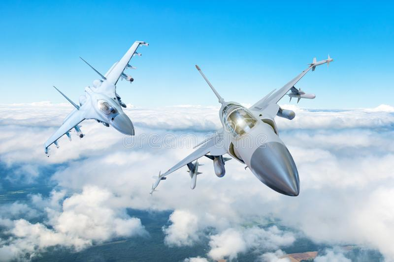 Pair of combat fighter jet on a military mission with weapons - rockets, bombs, weapons on wings flies high in the sky above the c stock photography