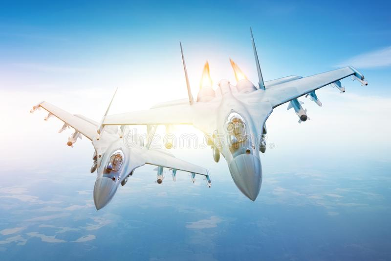 Pair of combat fighters, in conjunction flying in the sky over the territory stock image