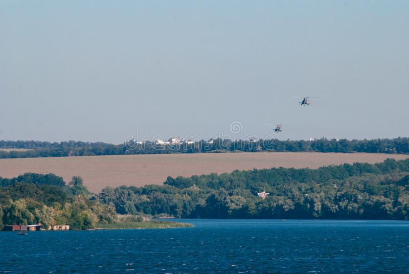 A pair of combat helicopters flying over the river stock image