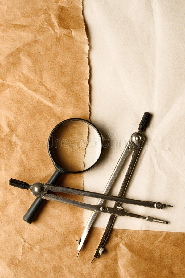 Pair of compasses and magnifying glas stock photography