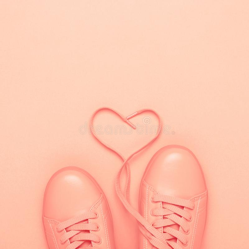 Pair of coral shoes on coral background. royalty free stock photo
