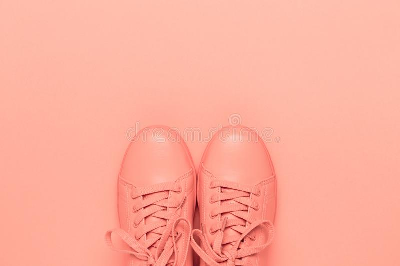 One pair of coral shoes on coral background. royalty free stock photo