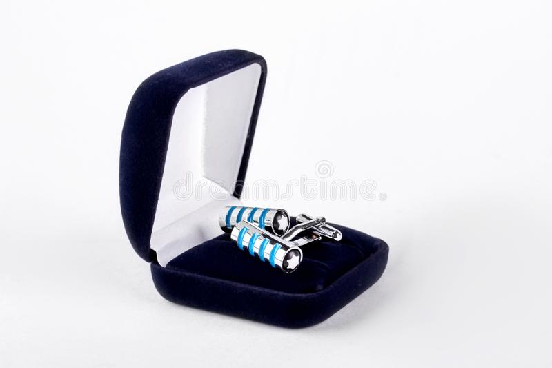 Pair of cuff links in velour box. Silver and blue wedding cuff links in velour box isolated on white background. Men elegance and style stock images
