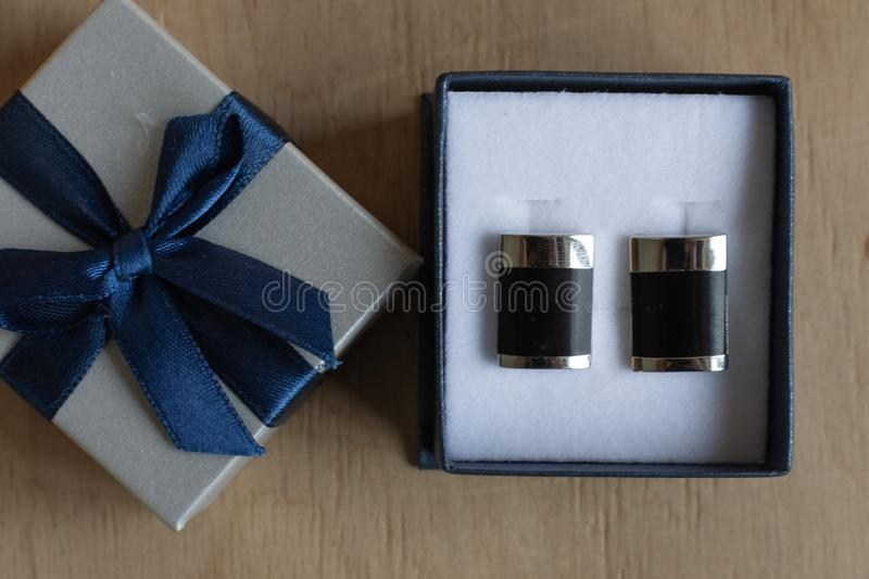 Pair of cufflinks in a gift box on wooden background. Fashion gift for man. Pair of cufflinks royalty free stock photos