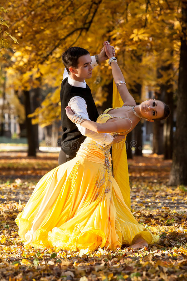Pair of dancers dancing in the woods. Man with suit, woman in yellow long dress middle of the palace park in autumn. Dry fallen c. Pair of dancers dancing in the royalty free stock photography