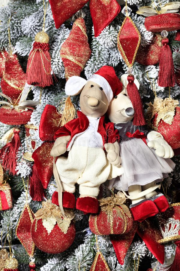 Pair of decorative toy mice is festively dressed in red clothes on the eve of the rat year on the background of the New Year tree royalty free stock photography
