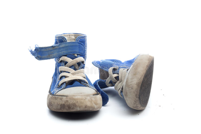 Pair of dirty, worn out blue children sneakers. Pair of dirty, worn out blue sneakers in children size, on white background stock images