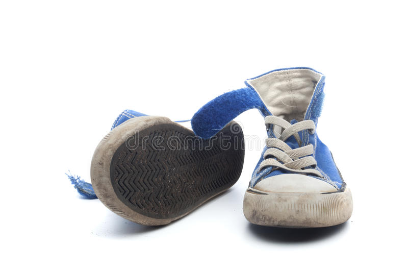 Pair of dirty, worn out blue children sneakers. Pair of dirty, worn out blue sneakers in children size, on white background royalty free stock photography