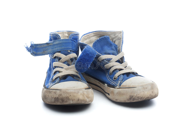 Pair of dirty, worn out blue children sneakers. Pair of dirty, worn out blue sneakers in children size, on white background stock photo