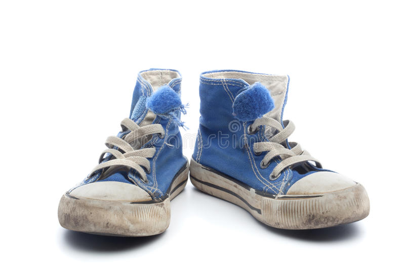 Pair of dirty, worn out blue children sneakers. Pair of dirty, worn out blue sneakers in children size, on white background royalty free stock photos