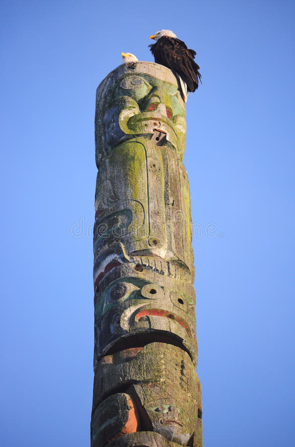 Pair of Eagles and Totem Pole. A pair of adult Eagles sit on top of a Canadian Native Indian totem pole carved out of wood stock photography