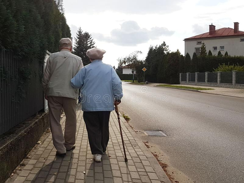 A pair of elderly people walk along the sidewalk along the road holding hands. Grandfather and grandmother on a walk in a royalty free stock photo