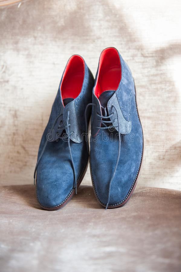 Pair of elegant blue suede shoes for men. Pair of elegant blue suede shoes with red interior for men on a satin chair royalty free stock photos