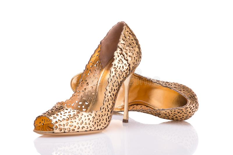 A pair of elegant shoes made of golden leather on a white background. Elegant gold leather shoes on a white background royalty free stock photo