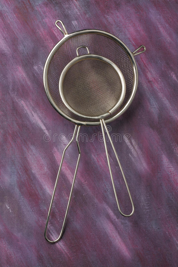 Pair of empty metal kitchen sieves. Pair of empty kitchen sieves over painted textile background. Overhead view royalty free stock images