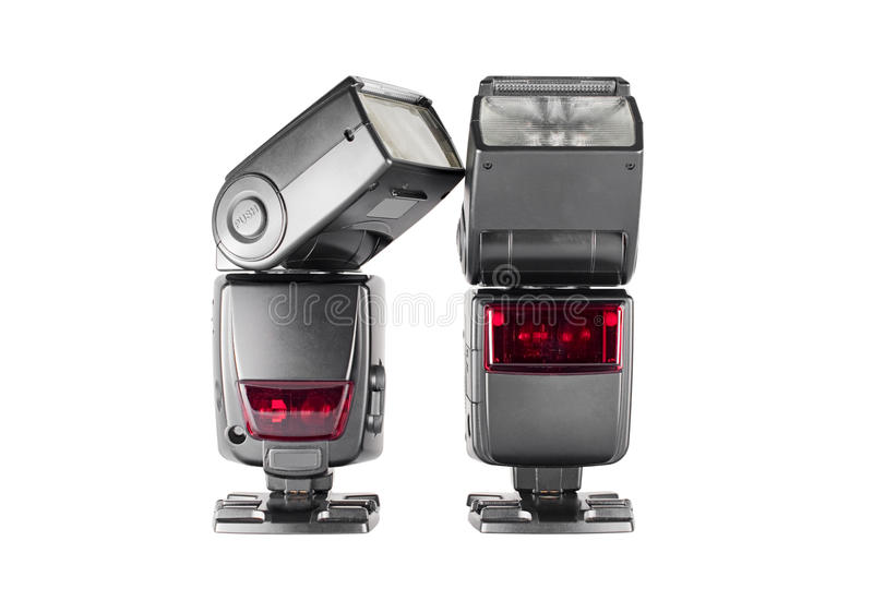 Pair of external flashes. Two external flashes on stands, isolated on a white background. The left flashhead is tilted to the right stock photos