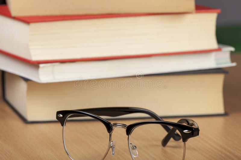 Pair of eyeglasses next to a pile of books stock photography
