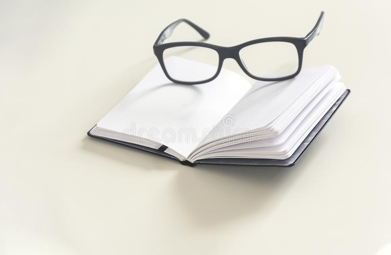 a pair of eyeglasses on an open notebook with blank pages royalty free stock photo