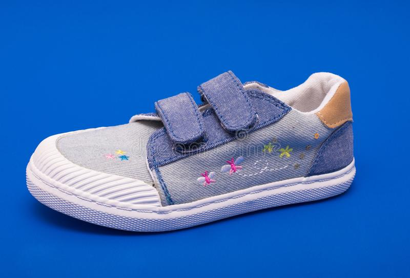 Pair of fashion denim baby shoes for the toddlers feet. Kids sneakers on blue background. stock photography