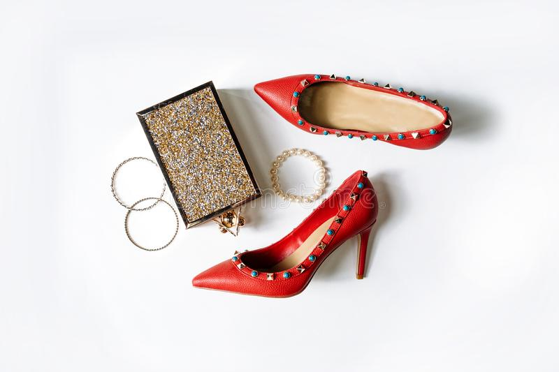 Pair of red high-heeled shoes with pointed toes, decorated with metal blue inserts and metal clutch with sparcles on a white. Pair of fashionable red high-heeled royalty free stock image