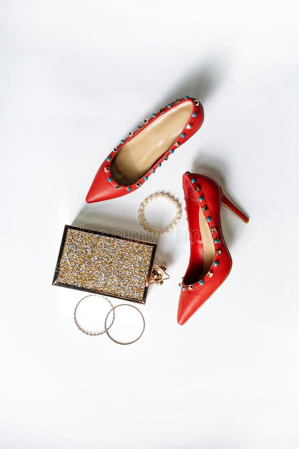 Pair of red high-heeled shoes with pointed toes, decorated with metal blue inserts and metal clutch with sparcles on a white. Pair of fashionable red high-heeled stock photo