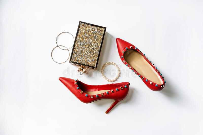Pair of red high-heeled shoes with pointed toes, decorated with metal blue inserts and metal clutch with sparcles on a white royalty free stock photography