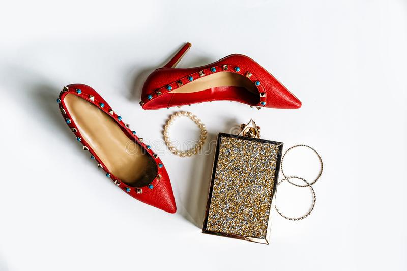 Pair of red high-heeled shoes with pointed toes, decorated with metal blue inserts and metal clutch with sparcles on a white stock photo