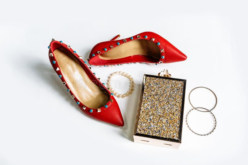 Pair of red high-heeled shoes with pointed toes, decorated with metal blue inserts and metal clutch with sparcles on a white. Pair of fashionable red high-heeled royalty free stock photo
