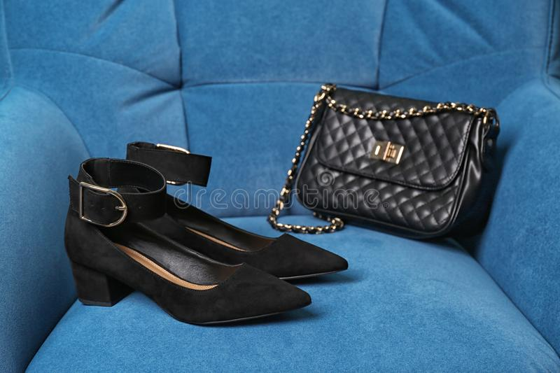 Pair of female shoes and bag. On armchair royalty free stock images