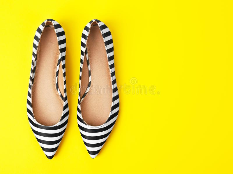 Pair of female shoes on color background stock photo
