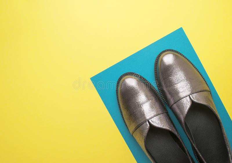 Pair of female shoes on yellow background. Pair of sparkly female shoes on yellow and blue background with copyspace. Flat lay style stock image