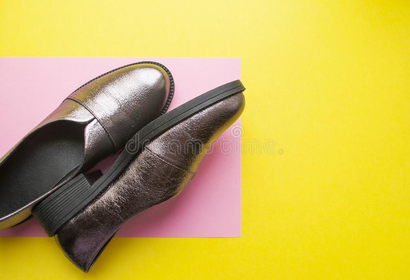 Pair of female shoes on yellow background. Pair of sparkly female shoes on yellow and pink background with copyspace. Flat lay style royalty free stock image