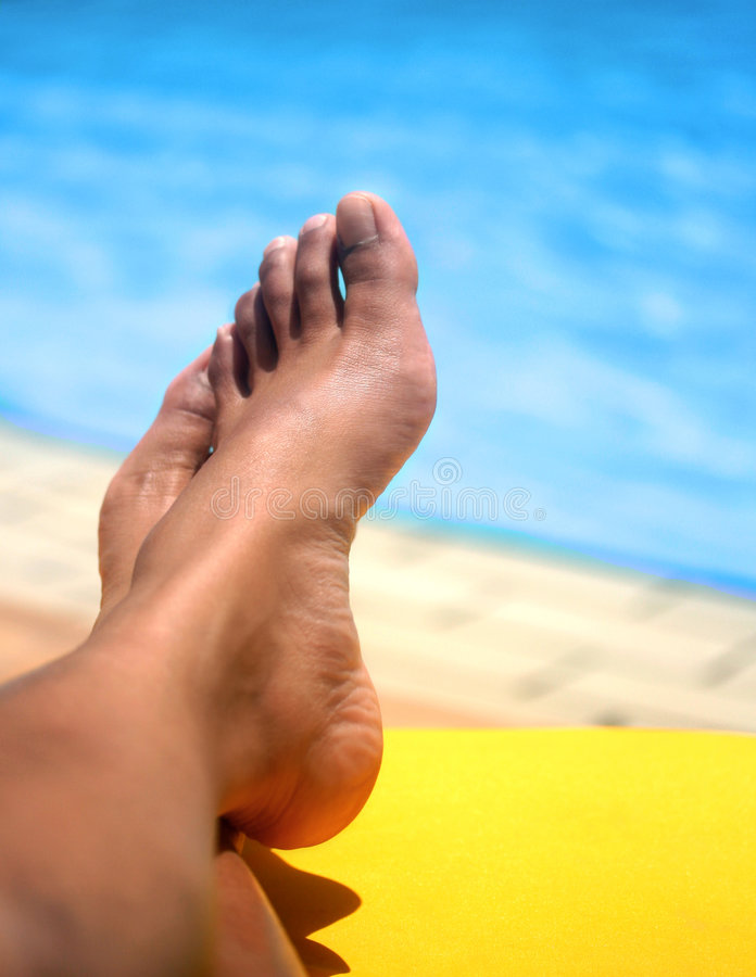 Pair of feminine feet resting on a sun lounger by the pool royalty free stock image