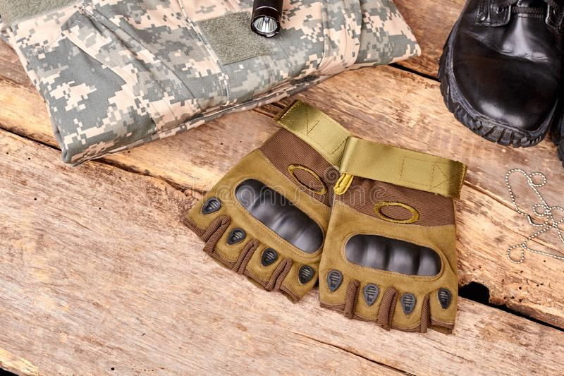 Pair of fingerless gloves and camouflage clothes on wood. Black shoe and torch. Flat lay, top view royalty free stock photography