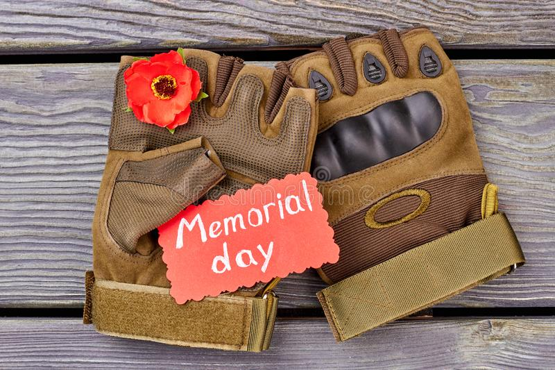Pair of fingerless gloves and red poppy. Grey wood background royalty free stock image