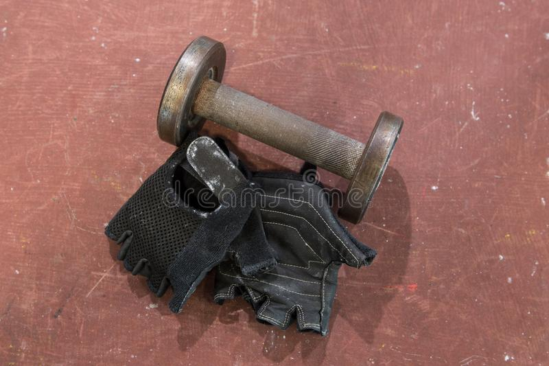 Pair of fitness black gloves with used small dumbbell against red, orange background, surface. Fitness and gym equipment, accessor. Pair of fitness black gloves stock images