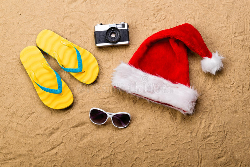 Pair of flip flop sandals, sunglasses, Santa hat and camera. Summer vacation composition with a pair of yellow flip flop sandals, Santa Claus hat, sunglasses royalty free stock photography
