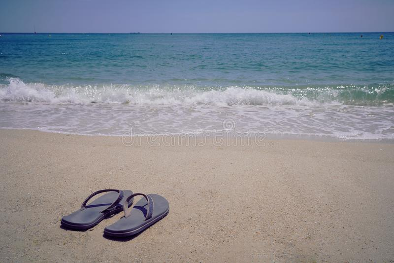 Pair of flip flops on the beach. One pair of flip flops at a beach in Brittany, focus on the shoes royalty free stock images