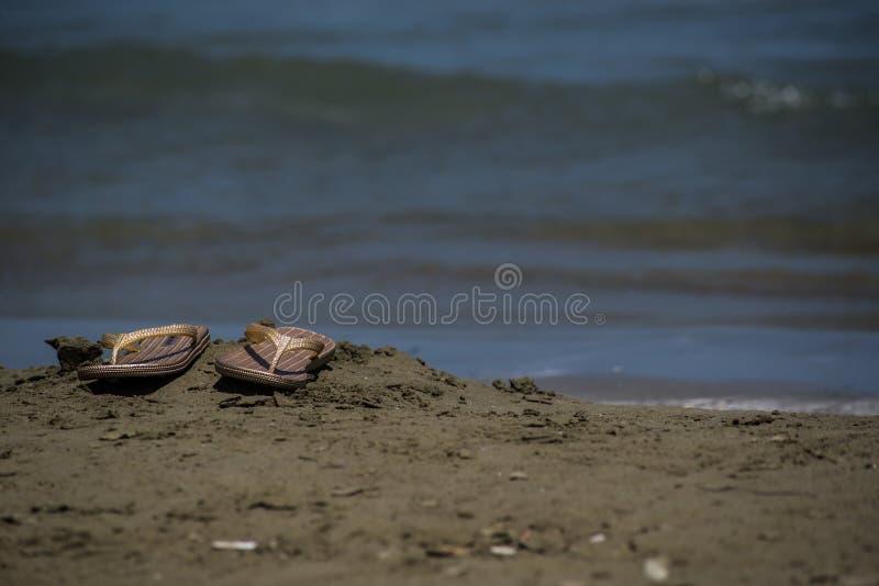 A pair of flip flops on the beach sand. A pair of flip flops, on the beach sand, colored without people. Closeup stock photos