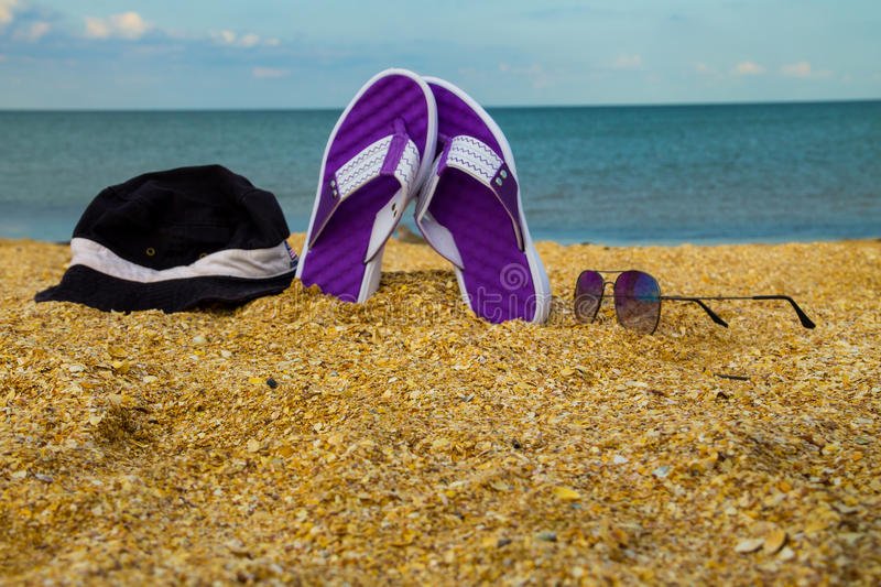 Pair of flip flops, hat and sunglasses on a sandy sea beach stock photography