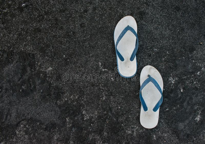 A pair of flip flops or slippers with blacl texture and abstract pattern roof background. White, grey, roof, blue, wall, paper royalty free stock photos