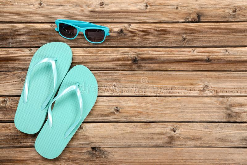 Flip flops with sunglasses. Pair of flip flops with sunglasses on brown wooden table stock photos