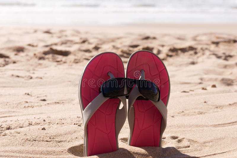 Pair flip flops with sunglasses in the sand of beach. Travel background stock images