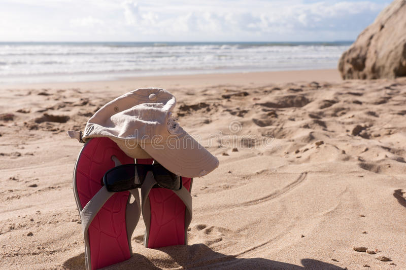 Pair flip flops with sunglasses in the sand of beach. Travel background stock photography