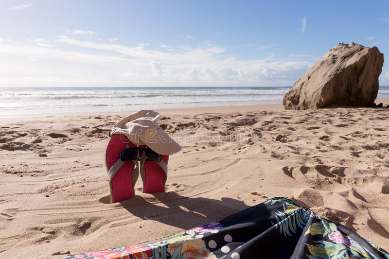 Pair flip flops with sunglasses in the sand of beach. Travel background stock photos