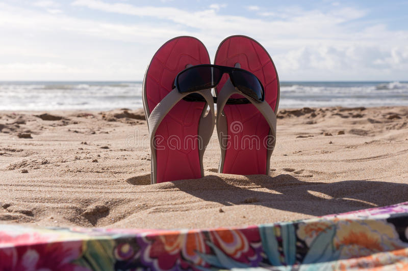 Pair flip flops with sunglasses in the sand of beach. Travel background royalty free stock photos
