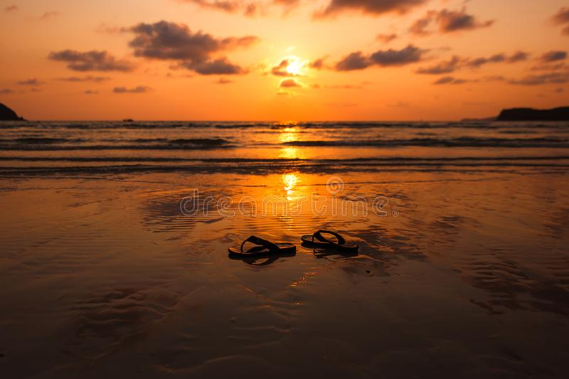 Pair of flip flops at sunset, sunrise time on the beach. Background concept stock photography